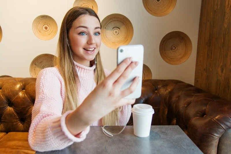 Young woman recording a video with a phone.