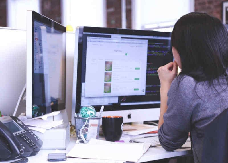 Web designer looking at code on her computer screen