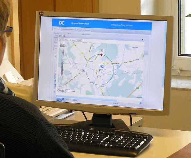 Woman looking at a computer with geofencing displayed on the monitor