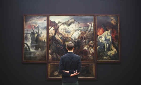 Man looking at large paintings in a museum.