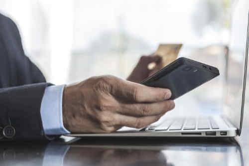 Man using laptop, phone and credit card